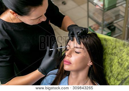 Beautician is preparing to inject botulinum toxin in female face. Middle age woman on cosmetological procedures. Beauty and wellness. Horizontal photo. stock photo