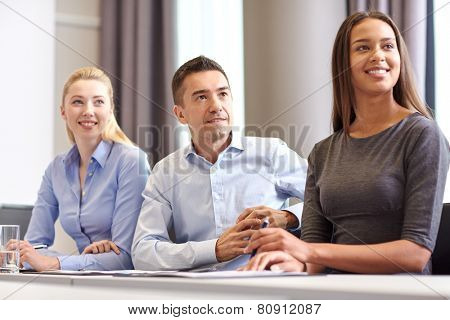 business, people and teamwork concept - group of smiling businesspeople meeting on presentation in o