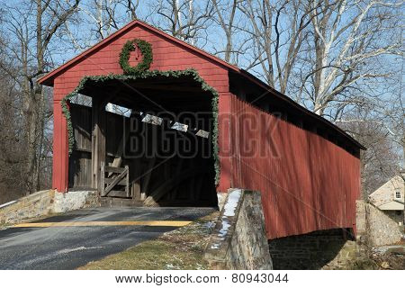 The Pool Forge Covered Bridge built in 1859 in Caernarvon Township Lancaster County Pennsylvania crosses the Conestoga River. Located now on private property it is decorated for the Christmas holiday. stock photo