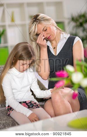 Sad girl sitting on sofa next worried mom at home  stock photo