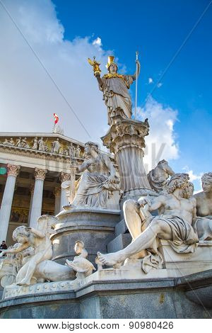Parliament building in Vienna, Austria. Statue and fountain of Pallas Athena Brunnen - greek goddess of wisdom - in front of it against the blue cloudy sky stock photo