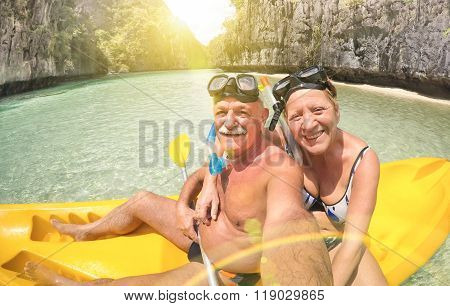Senior happy couple taking selfie on kayak at Big Lagoon in El Nido Palawan - Travel to Philippines wonders - Active elderly concept around the world - Lens flare and sun halo are part of composition stock photo