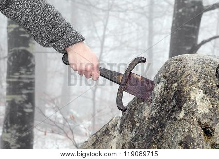 Hand of the valiant knight tries to remove the magical Excalibur sword in the stone stock photo