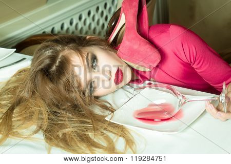 Sensual elegant glamour young drunk woman with beautiful hair lying on table with glass and poored red wine in plate after hangover with suide shoe horizontal picture stock photo