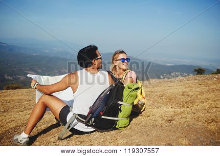 Two cheerful best friends looking back on the mountain which they overcame during walking tour in sunny day stock photo