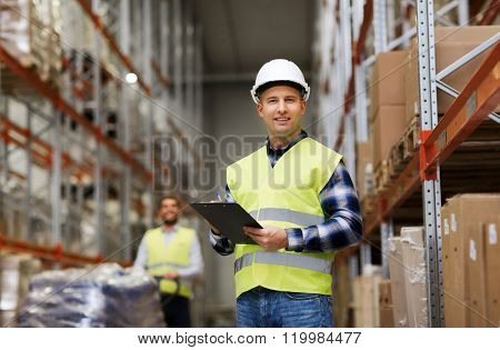 wholesale, logistic, people and export concept - man with clipboard in reflective safety vest at war