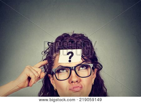Thinking perplexed woman with question mark isolated on gray wall background. Thoughtful girl scratching head looking up solving a problem