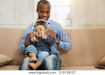 Enjoying music. Good-looking gleeful afro-american man holding his little son and putting headphones on him while sitting on the couch stock photo