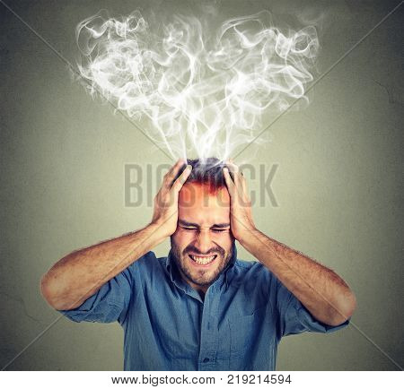 Portrait young stressed man screaming thinking too hard steam coming out up of head isolated on grey wall background. Face expression emotion perception stock photo