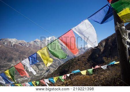 Buddhist prayer flags lungta in the Himalaya mountains, Annapurna region, Nepal near Milarepa cave stock photo
