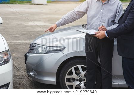 Insurance Agent examine Damaged Car and filing Report Claim Form after accident Traffic Accident and insurance concept. stock photo