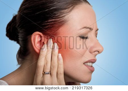 Tinnitus. Closeup up side profile sick female having ear pain touching her painful head isolated on blue background stock photo