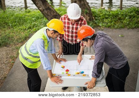 engineer and construction team wearing safety helmet and looking blueprint on the table. they are working on checking progress of construction site. engineer and client reviewing material and checking construction process in construction site area. stock photo