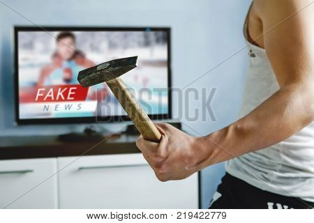 A psychopath wants to crash the TV with a hammer. The viewers got tired of false news. Truth misrepresented in the news on a modern TV. fake news report. Zombie TV. Deception of viewers. stock photo