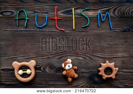 Diseases. Infantile autism. Word with colored letters on dark wooden background top view background top view. stock photo