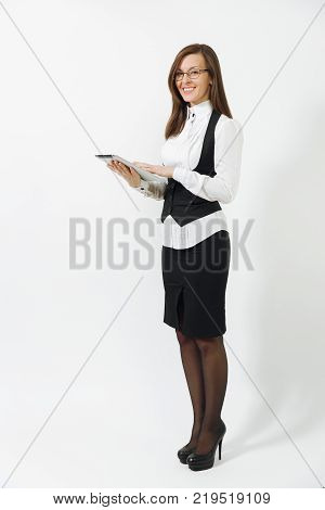 Pretty engrossed brown-hair business woman in suit earphones and glasses sitting at the desk with cup of coffee mobile phone working at computer with modern monitor with document in light office stock photo