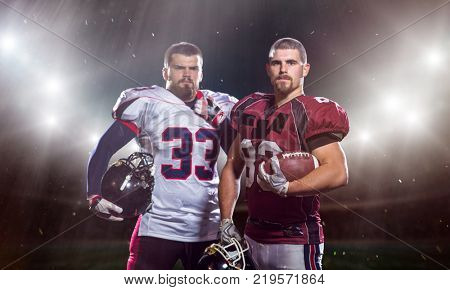 portrait of confident American football players holding ball while standing on big modern american football stadium field with flares and lights stock photo