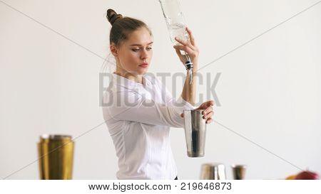 Professinal bartender girl juggling bottles and shaking cocktail at mobile bar table on white background studio indoors stock photo
