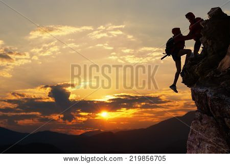 Teamwork hiking help each other trust assistance at mountains and beautiful sunrise,teamwork and hiking concept.