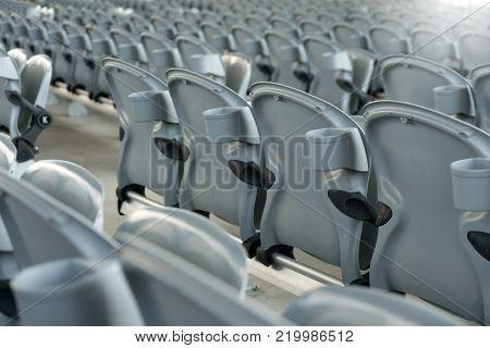 White plastic folding empty red seats in concert or football stadium. Row of football sport stadium seats with sunlight. stock photo