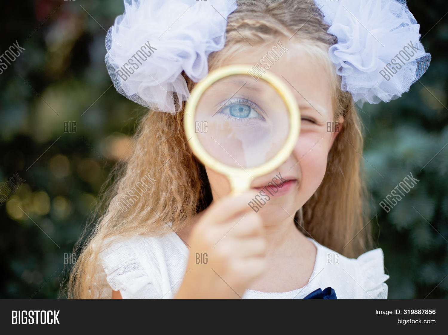 Portrait Of Beautiful Young Schoolgirl Looking Through Magnifying Glass