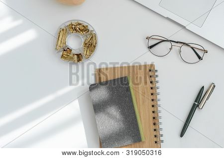 Home office desk workspace with blank copy space clipboard, laptop, headphones, glasses, succulent o