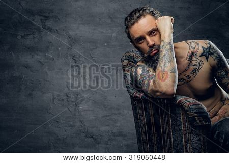 Bearded sad man is sitting in old armchair at abandoned house alone and thinking about his life. stock photo