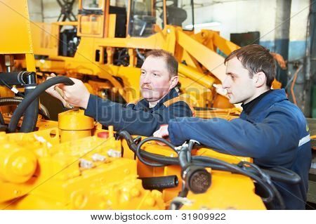 adult experienced industrial workers during heavy industry machinery assembling on production line manufacturing workshop stock photo