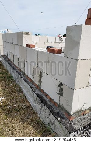 Laying the wall of gas blocks with tools and glue. stock photo