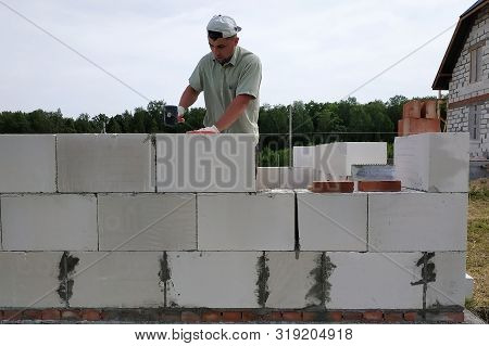 The master performs construction work, namely, laying a wall of gas blocks with tools and adhesive mortar, in the background the sky and the forest. stock photo