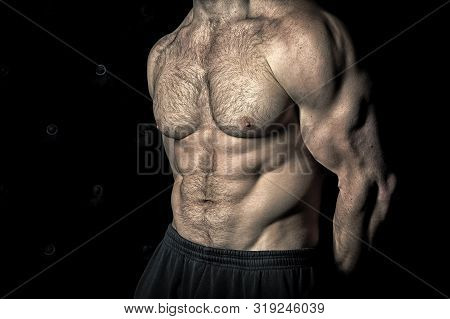 Preparing muscles for actions. Torso with six packs looks attractive on black background. Muscular torso huge muscles result of exhausting trainings and proper nutrition. Achieve muscular torso tips. stock photo