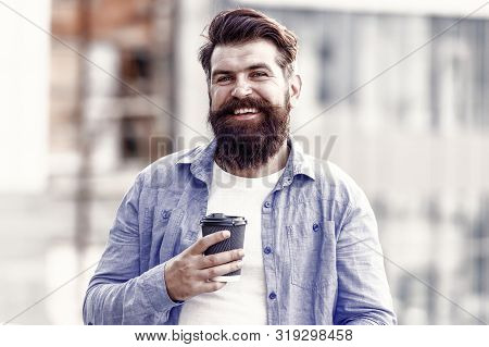Make yourself useful. Man drink take away coffee. Bearded man relax outdoors. Coffee break concept. Caffeine addicted. Morning coffee. Mature hipster enjoy hot beverage. Coffee completes me. stock photo