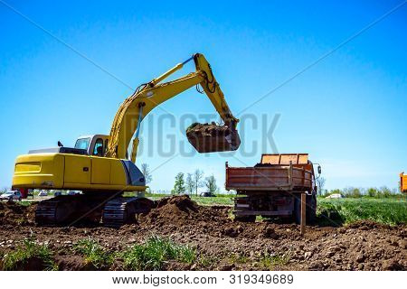 Big excavator is filling a dumper truck with soil at construction site, project in progress. stock photo