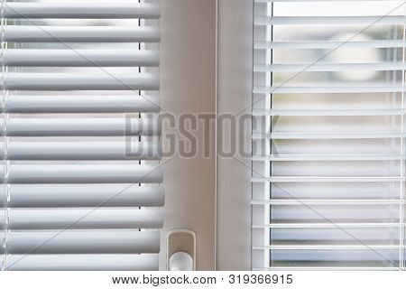 Closeup view of window with horizontal blinds. White Roller Blinds or Louver curtains at the glass window stock photo
