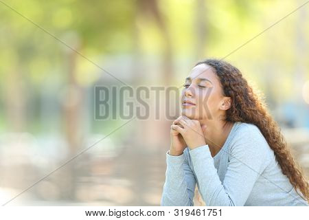 Mixed-race woman relaxing meditating sitting outdoors in a park stock photo