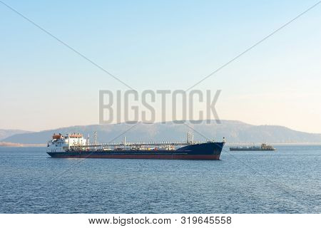Cargo ship on the background of mountains. Oil tanker anchored. At the top there is a place for your text. Next to a small floating barge. stock photo