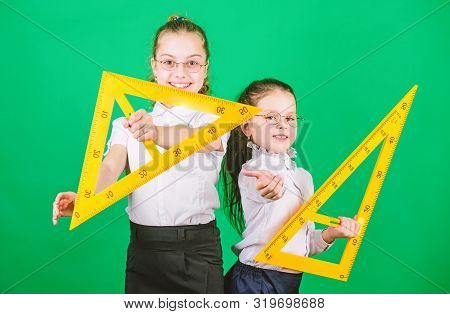 Geometry favorite subject. Education and school concept. School students learning geometry. Kids school uniform green background. STEM school disciplines. Classmates cute girls with big rulers stock photo
