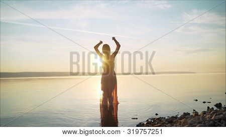 Girl in a light dress on the beach at sunrise. beautiful women in a light pink dress walking along the beach at dawn. Good morning and relaxation. Young beautiful girl stands in the water in a light pink dress on the background of the dawn. stock photo