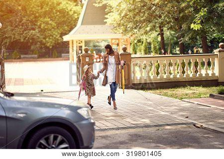 schoolgirl going back to school. Mother and happy kid going to school.
