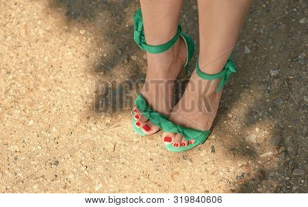 Beautiful Legs Of A Girl In Retro Sandals On Heels. A Beautiful Red Pedicure Has A Shine In The Sunl