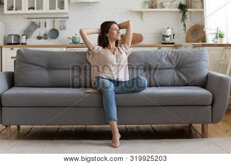 In cozy living room happy woman sitting on couch alone stock photo