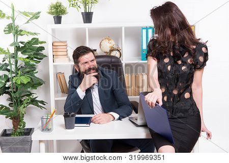 Loved by his employee. Sexy administrative employee and employer. Adorable woman employee sitting at desktop while man looking at her. Professional female employee at workplace against businessman. stock photo