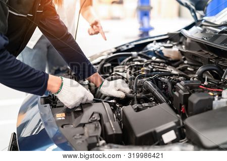 Mechanic asian man examining and maintenance to customer the engine a vehicle car hood, Safety inspection test engine before customer drive on a long journey, transportation repair service center stock photo