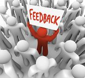 A gathering of individuals with one red individual lifting a sign perusing Feedback, speaking to the