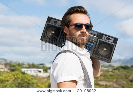 Portrait of a handsome young man holding radio near ears. Close up of hipster guy listening to music