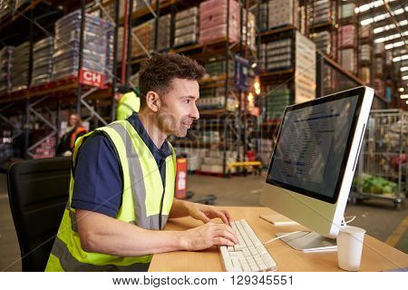 Man working in on-site office at a distribution warehouse