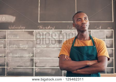 Handsome young craftsman of African descent standing with his arms folded and wearing an apron, thinking about his entrepreneurial future plans stock photo