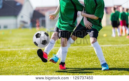 Soccer players running with ball. Children playing soccer in organized youth game. Young boys child in sportswear training soccer on a sports field.