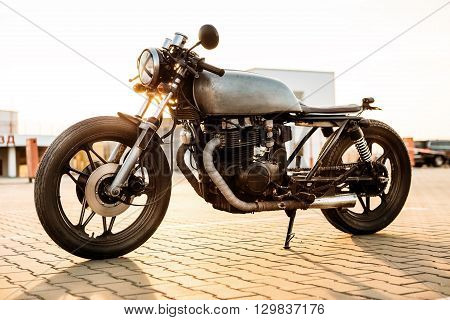 One silver vintage custom motorbike caferacer motorcycle on empty rooftop parking lot surrounded by urban environments midtown buildings during sunset. Hipster lifestyle student dream. stock photo