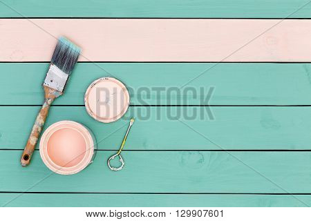 Top down view of paintbrush bolt paintcan and green boards for paneling or flooring starting to be painted pink stock photo